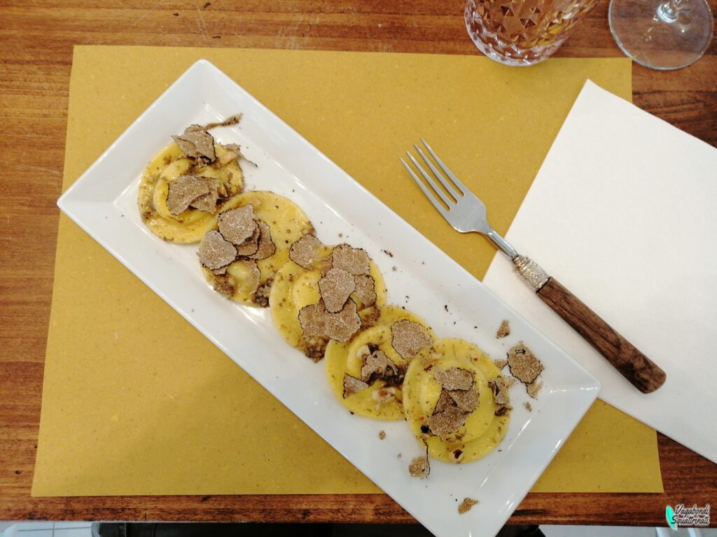 ravioli freschi ripieni di ricotta e burrata con colatura di alici, tartufo e nocciole